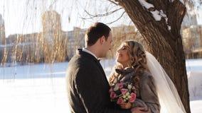 Le persone appena sposate si riscaldano nella neve in un parco dell'inverno stock footage