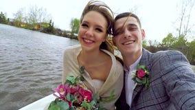 Le persone appena sposate stanno guidando la barca dallo stagno e stanno facendo i selfies luminosi Fine in su archivi video