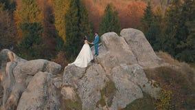 Le persone appena sposate stanno su un alto pendio della montagna Sposo e sposa Vista di Arial fotografia stock libera da diritti