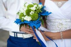 Le persone appena sposate stanno tenendo un mazzo di nozze nei colori bianchi e verdi ed in decorazione blu immagine stock libera da diritti