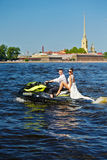 Le persone appena sposate vanno sui jet ski, sulla sposa e sullo sposo sui precedenti Fotografie Stock
