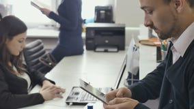 Le persone di affari stanno lavorando con la compressa ed il computer portatile nell'ufficio archivi video