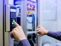 Le personnel abaissent la machine de contrôle électronique avec le balayage de doigt pour accéder à la porte de la salle de comma images stock