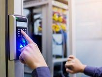 Le personnel abaissent la machine de contrôle électronique avec le balayage de doigt pour accéder à la porte de la salle de comma photographie stock