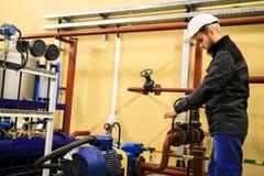 Le personnel d'entretien vérifie des capteurs de pression sur la canalisation à l'usine de chauffage de chaudière photographie stock