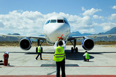 Le personnel de piste guide un avion à réaction à la porte Images libres de droits