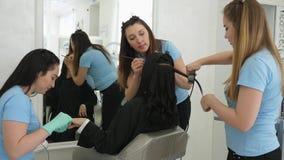 Le personnel de service du salon de beauté composent et coiffure pendant la manucure pour le plan rapproché de client clips vidéos