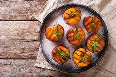 Le pesche mature hanno grigliato con lo zucchero e la menta in polvere su un piatto Uff Immagine Stock