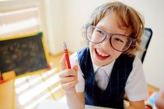 Le petit écolier drôle en verres s'assied à un bureau d'école Image libre de droits