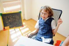Le petit écolier vilain en verres rit gaiement Image libre de droits