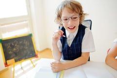 Le petit étudiant gai à lunettes s'assied au bureau d'école Photographie stock libre de droits