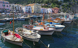 Le petit asile avec des bateaux de pêche et des maisons de colorfull est situé dessus par l'intermédiaire de del Mare à Sorrente Photos stock