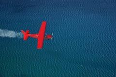 Le petit avion rouge vole au-dessus d'une mer images stock