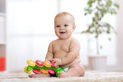 Le petit bébé adorable dans la couche-culotte s'assied sur le tapis et joue avec le jouet à la maison Profondeur de zone Photographie stock libre de droits