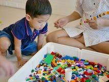 Le petit bébé asiatique étant les briques en plastique de verrouillage colorées de regard intéressées jouent photo libre de droits