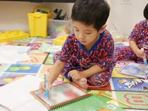 Le petit bébé asiatique laissé a plaisir la peinture photo libre de droits