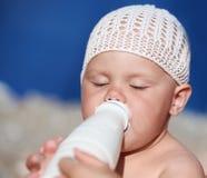 Le petit bébé boit du lait de la bouteille Image libre de droits
