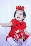 Le petit bébé chinois heureux dans le cheongsam rouge ont l'amusement Photographie stock libre de droits