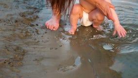 Le petit bébé dans des couches-culottes joue sur la plage par la rivière L'enfant éclabousse ses mains dans l'eau Plan rapproché  clips vidéos
