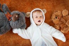 Le petit bébé dans le costume d'ours avec la peluche joue Images stock