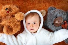 Le petit bébé dans le costume d'ours avec la peluche joue Photo libre de droits