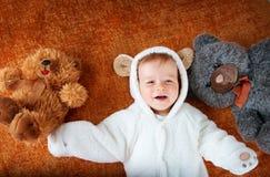 Le petit bébé dans le costume d'ours avec la peluche joue Images libres de droits
