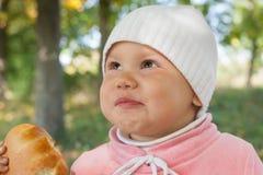 Le petit bébé en parc d'automne mange le tarte Image stock