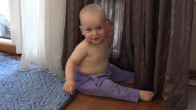 Le petit bébé garçon heureux dans le pantalon jouent près du rideau Garçon de sourire regardant l'appareil-photo clips vidéos