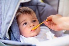 Le petit bébé garçon mange tout en se reposant dans une voiture d'enfant photo libre de droits