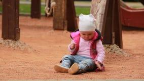 Le petit bébé mignon s'est habillé dans l'habillement rose se reposant sur le terrain de jeu dans extérieur banque de vidéos