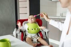Le petit bébé nouveau-né s'asseyant dans la chaise de bébé avec des restes près de la bouche pleure et refuse de manger tandis qu photos stock