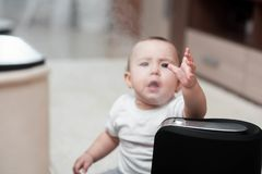 Le petit bébé regarde l'humidificateur Humidité dans le concept de maison photo stock