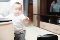 Le petit bébé regarde l'humidificateur Humidité dans le concept de maison photographie stock libre de droits