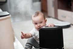Le petit bébé regarde l'humidificateur Humidité dans le concept de maison photos libres de droits
