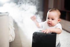 Le petit bébé regarde l'humidificateur Humidité dans le concept de maison image libre de droits