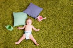 Le petit bébé se trouve sur le tapis vert Photos stock