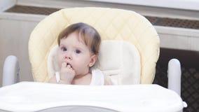 Le petit bébé, suce le poing, se reposant sur une chaise d'arbitre dans la cuisine clips vidéos