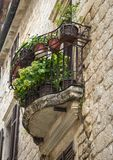 Le petit balcon semi-circulaire avec la balustrade en métal, calent avec des fleurs dans des pots dans la ville de Kotor, Monténé photo stock