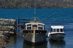 Le petit bateau et le bateau attachés en Lago Puelo hébergent Photo libre de droits