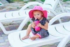 Le petit bébé en parc d'automne boit de la bouteille en plastique rose Images stock