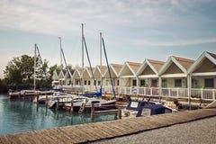 Le petit beau cottage d'été sur le Neusiedler voient le lac avec un pilier pour des bateaux et des yachts Photos stock