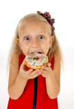 Le petit bel enfant féminin avec de longs cheveux blonds et robe rouge mangeant le beignet de sucre avec des écrimages a enchanté Images libres de droits