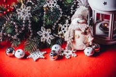 Le petit bonhomme de neige adorable mignon se tient près de la lanterne féerique blanche et de la branche d'arbre décorée de sapi Image stock