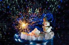 Le petit bonhomme de neige avec des feux d'artifice miroite d'un plat avec des guimauves et des bonbons orientaux photographie stock libre de droits