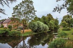 Le petit canal avec du charme à côté de la maison rustique avec le jardin luxuriant et les arbres ont réfléchi sur l'eau dans le  photo libre de droits