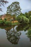 Le petit canal avec du charme à côté de la maison rustique avec le jardin luxuriant et les arbres ont réfléchi sur l'eau dans le  photos libres de droits