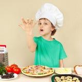 Le petit chef drôle expressif apprécie la pizza cuite images stock