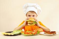 Le petit chef drôle goûte l'hamburger cuit Photos libres de droits