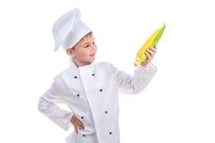 Le petit chef regarde le maïs frais jaune lumineux, d'isolement sur le fond blanc image stock