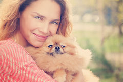 Le petit chien de Pomeranian et joli jouer de femme extérieurs Photographie stock libre de droits